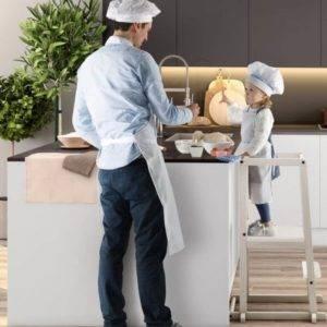petite fille regardant son papa qui cuisine depuis sa tour d'observation