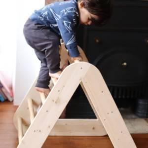 petit garçon sur le triangle de pikler