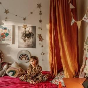 petite fille assise sur son lit devant son ciel de lit