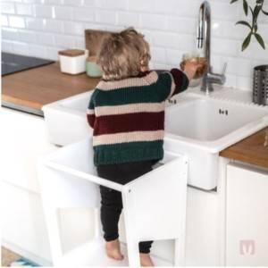 petit garçon se lavant les mains grâce à sa tour d'apprentissage