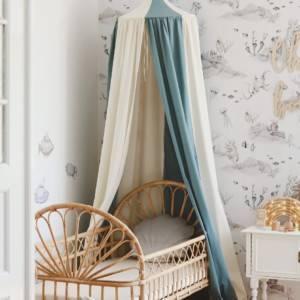ciel de lit bicolore bleu et blanc habillant un lit en rotin