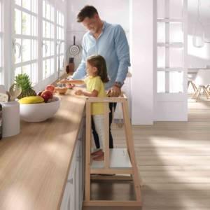 petite fille sur sa tour d'apprentissage micuna cuisinant avec son père