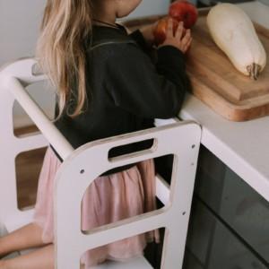 petite fille cuisinant dans la cuisine grâce à sa tour montessori blanche